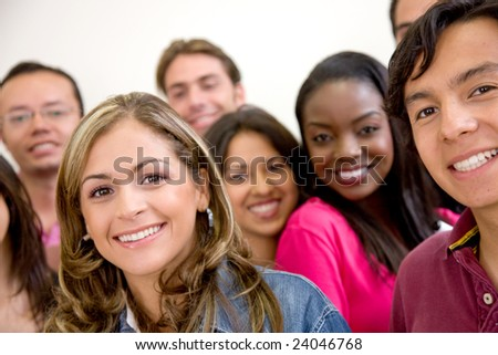 Multi-ethnic group of university students smiling in a classroom - stock photo