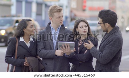 multi ethnic group of young friends having a discussion together in the city. diverse team of business professionals looking at tablet computer screen talking chatting about new ideas