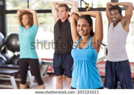 Multi-ethnic group stretching in a gym before their exercise class - stock photo