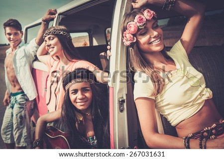 Multi-ethnic hippie friends with guitar on a road trip - stock photo