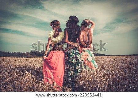 Multi-ethnic hippie girls  in a wheat field  - stock photo
