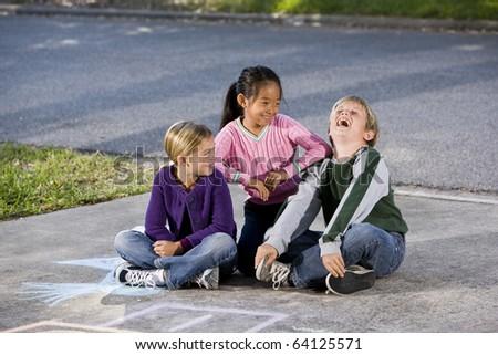 Multi-ethnic kids laughing together.  Girls 7 year, boy 9. - stock photo