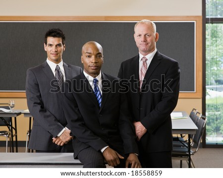 Multi-ethnic male co-workers posing in conference room - stock photo