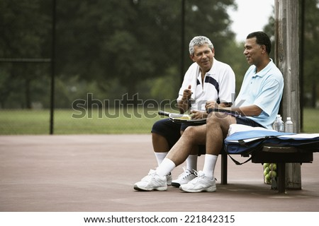 Multi-ethnic men talking on tennis court - stock photo