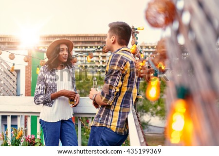 Multi-ethnic millenial couple flirting while having a drink on rooftop terrasse at sunset - stock photo