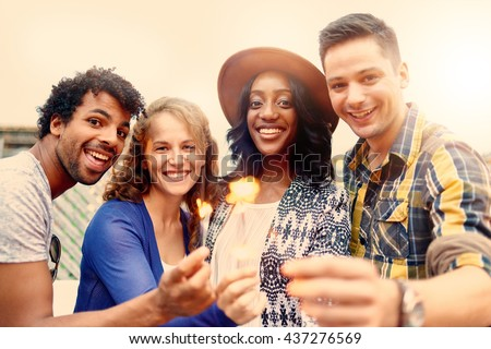 Multi-ethnic millenial group of friendsfolding sparklers on rooftop terrasse at sunset - stock photo