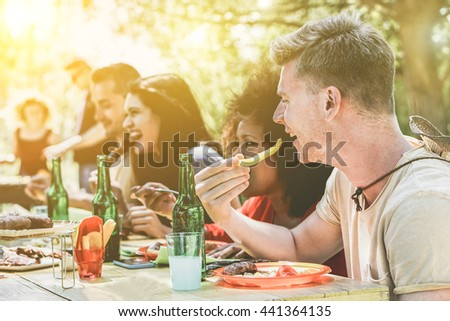 Multi ethnic people group enjoying grill meal at backyard barbecue meeting - Young friends having bbq party - Lunch and dinner concept outdoors - Soft focus on blond guy - Vintage retro filter - stock photo