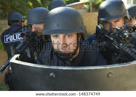 Multi ethnic policemen aiming guns while standing behind shield - stock photo