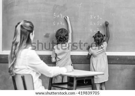 Multi ethnic primary school classroom writing with chalk at blackboard. - stock photo