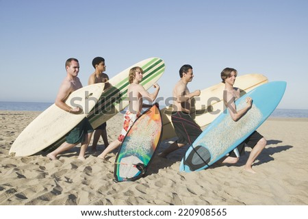 Multi-ethnic surfers holding surfboards and flexing on beach - stock photo