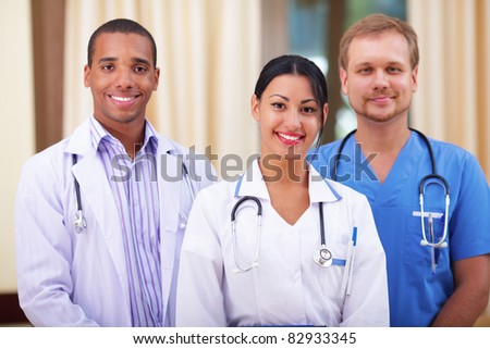 Multi-ethnic team of confident happy doctors - stock photo