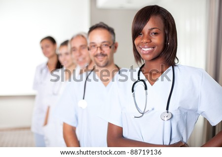 Multi-ethnic team of confident happy doctors standing in a row at the hospital