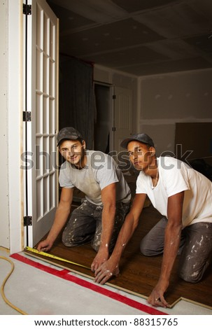 Multi ethnic team working on flooring in basement - stock photo
