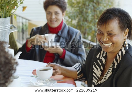 Multi-ethnic women having coffee outdoors - stock photo