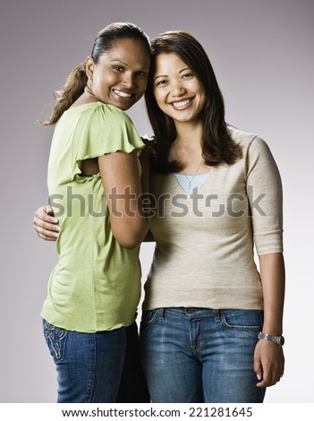Multi-ethnic women hugging - stock photo