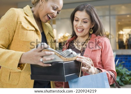 Multi-ethnic women looking at new shoes - stock photo