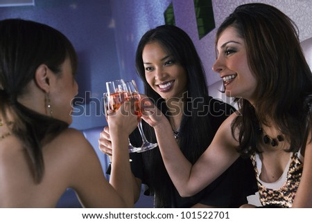 Multi-ethnic women toasting with cocktails - stock photo