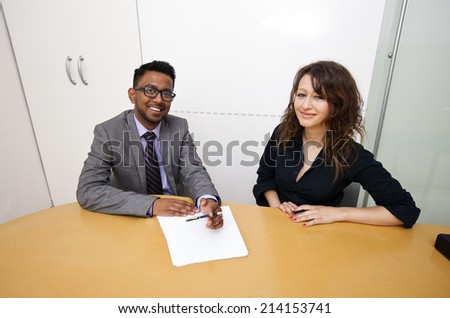Multi-ethnic work colleagues signing paperwork on a table - stock photo