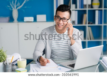 Multi-ethnic young man calling on the phone and making notes