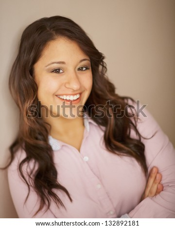 Multi ethnic young woman with perfect smile leaning on wall - stock photo