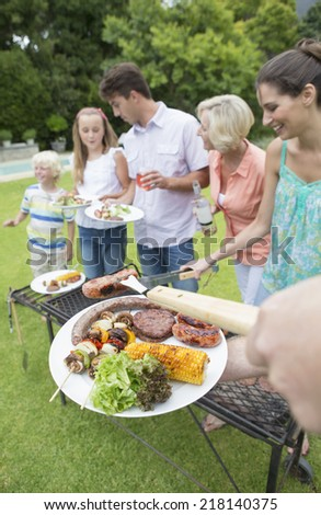 Multi-generation family at barbecue grille - stock photo