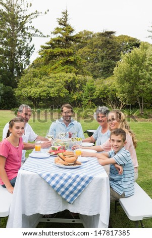 Multi generation family at picnic table having dinner outside smiling at camera - stock photo