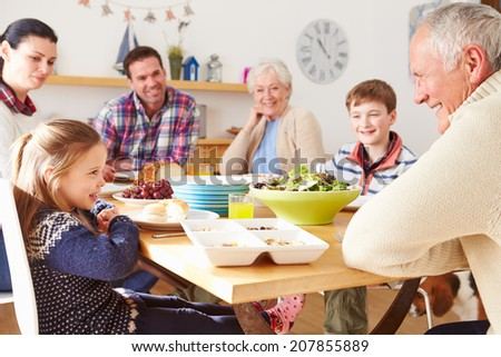 Multi Generation Family Eating Lunch At Kitchen Table - stock photo