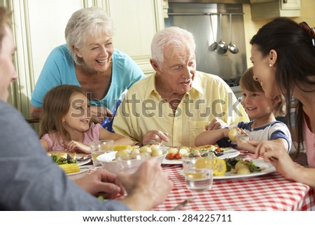 Multi Generation Family Eating Meal Together In Kitchen - stock photo