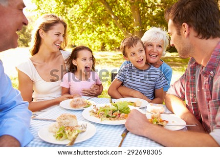 Multi-generation family eating together outdoors - stock photo