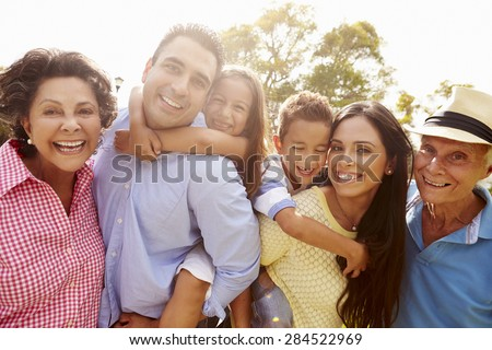 Multi Generation Family Having Fun In Garden Together - stock photo