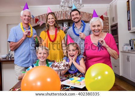 Multi-generation family in party hats having fun at birthday party - stock photo