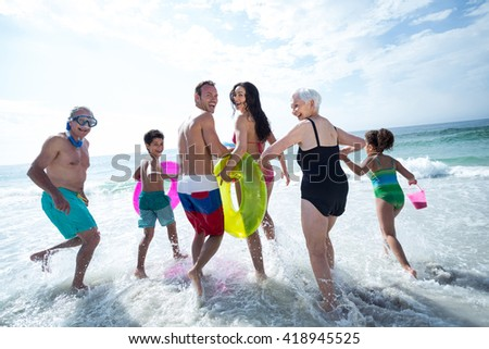 Multi- generation family laughing while running on sea shore at beach - stock photo