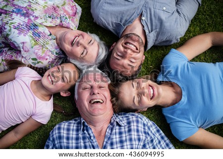 Multi-generation family lying together in the garden on a sunny day - stock photo
