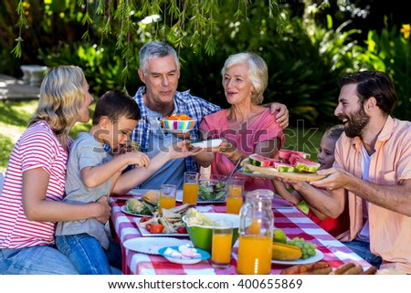 Multi- generation family offering food to each other at breakfast - stock photo