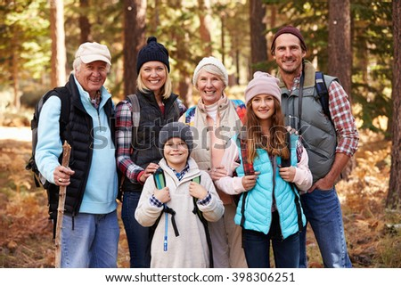 Multi generation family on hike in forest, group portrait - stock photo