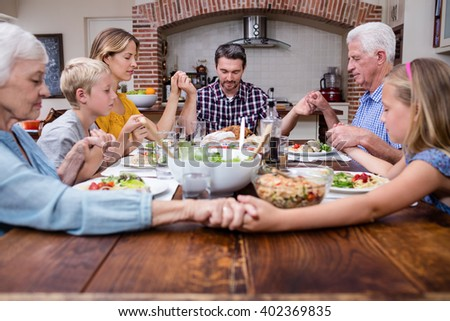 Multi-generation family praying before having meal at home - stock photo