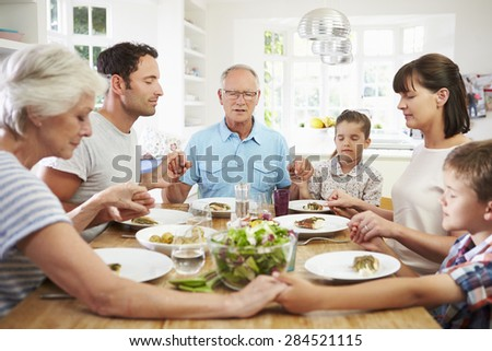 Multi Generation Family Praying Before Meal At Home - stock photo