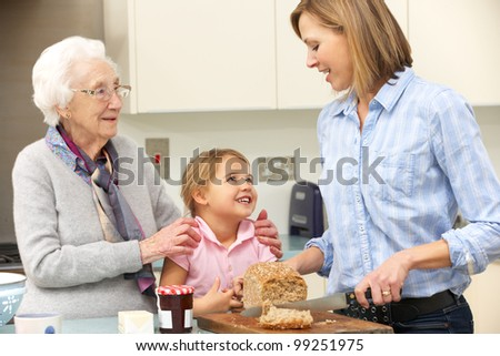 Multi-generation family preparing food in kitchen - stock photo