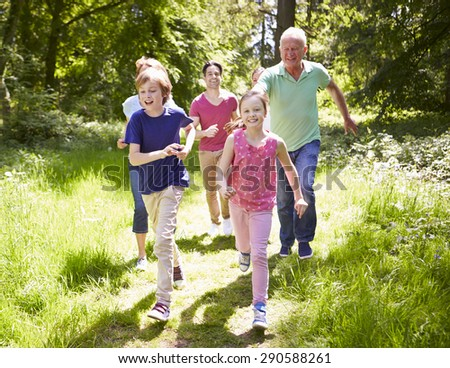 Multi Generation Family Running Through Summer Countryside - stock photo