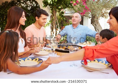 Multi Generation Family Saying Prayer Before Meal Together - stock photo