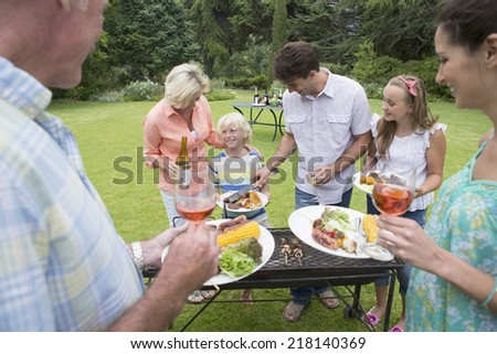 Multi-generation family serving barbecue - stock photo