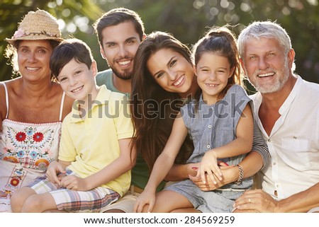 Multi Generation Family Sitting In Garden Together