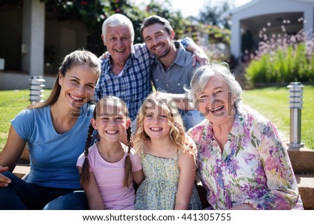Multi-generation family sitting in the garden on a sunny day - stock photo