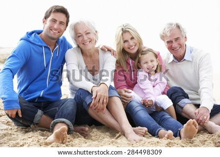 Multi Generation Family Sitting On Beach Together - stock photo