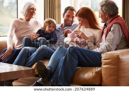 Multi Generation Family Sitting On Sofa With Newborn Baby - stock photo