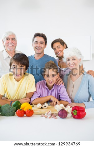 Multi generation family smiling in kitchen beside chopping board - stock photo