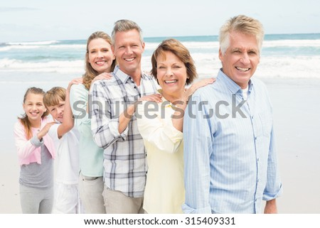Multi generation family standing beside one another at the beach - stock photo