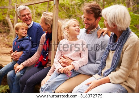 Multi-generation family talking on a bridge in a forest - stock photo