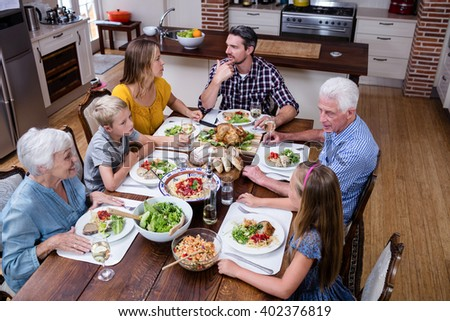 Multi-generation family talking while having meal in kitchen at home - stock photo