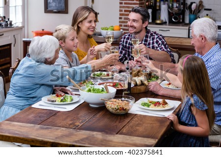 Multi-generation family toasting glass of wine while having meal